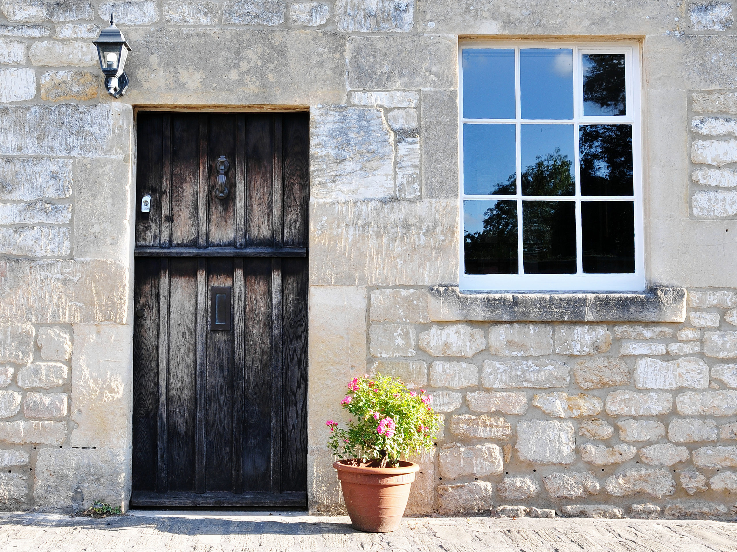 Traditional house with black front door and flowers next to door