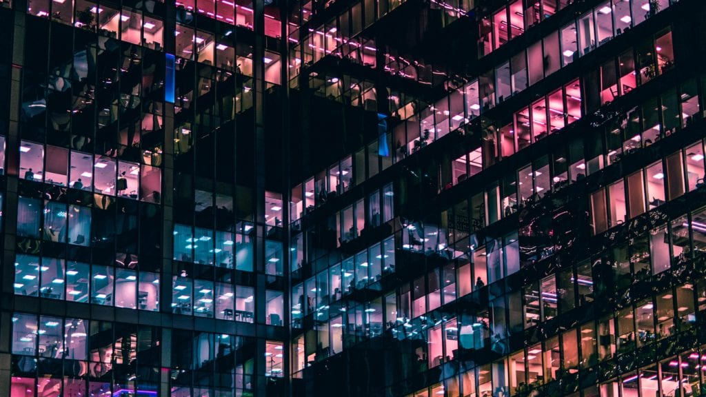 Windows of office blocks with workers sat in them at night