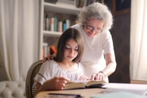 granddaughter reading a book with grandmother