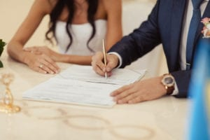 married couple signing wedding register at table